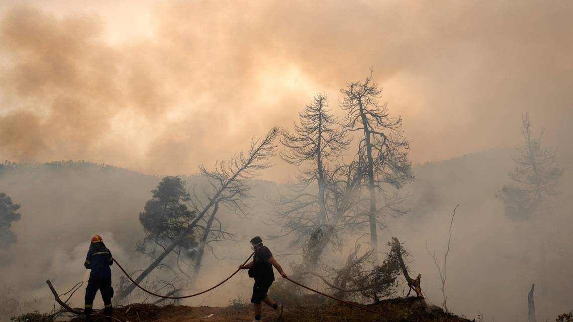 Fotografía tomada el lunes 9 de agosto de 2021. Un bombero combate las llamas al tiempo que un civil sostiene una manguera durante un incendio forestal en la aldea de Ellinika, en la isla de Evia, aproximadamente a 176 kilómetros al norte de Atenas